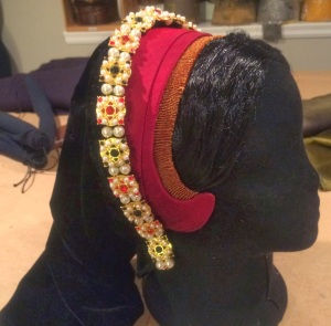 A French Hood by Truly Hats covered in jeweled ouches and pearls.